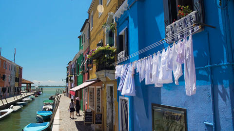 Female tourists go shopping in colorful street of Burano island in Venice Lagoon Footage