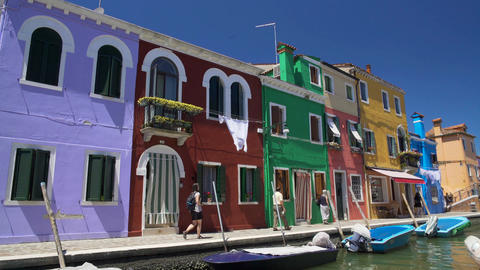 Curious tourists walking street on Burano island, photographing colored houses Footage