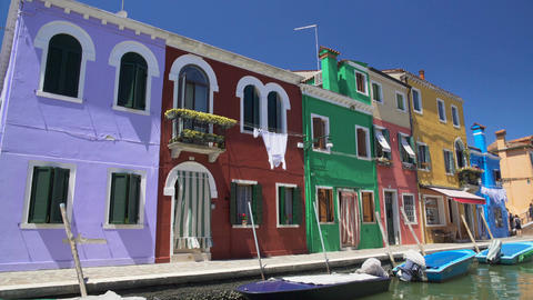 Brightly colored houses and boats at mooring points along canal on Burano island Footage