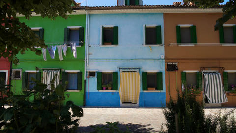 Colorful street with multicolored houses, laundry drying in wind, green plants Footage