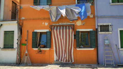 Shabby facade of old orange house with drying laundry and fishing equipment Footage