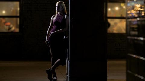 Beautiful female waiting for boyfriend near nightclub entrance, loneliness Footage