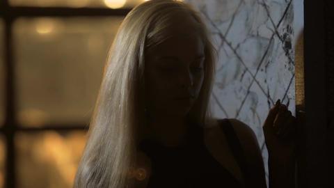 Lonely elegant female inhaling cigarette smoke, standing near nightclub entrance Footage