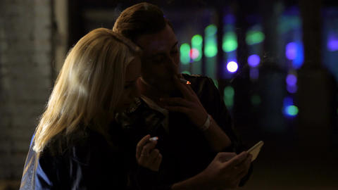 Young couple smoking cigarettes and looking through photos on smartphone Footage