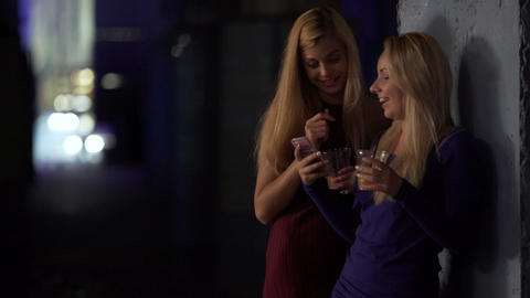 Two females drinking cocktails and looking through photos on smartphone, gossip Footage