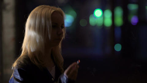 Young depressed woman smoking nervously near night club, loneliness, break-up Footage
