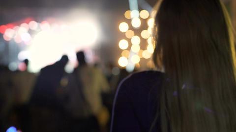 Beautiful woman waving blonde hair and dancing at music festival, illumination Footage