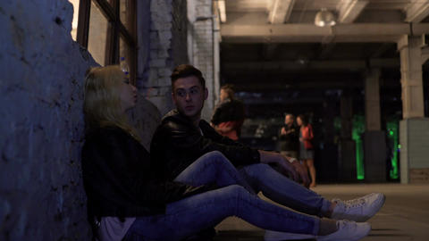 Blonde woman and man sitting near wall and talking, after-party, night life Footage