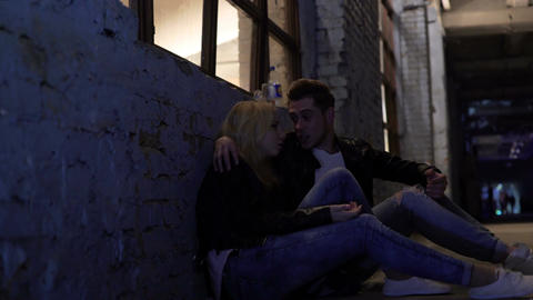 Drunk couple sitting on floor near wall and talking, nightlife, hook-up Footage