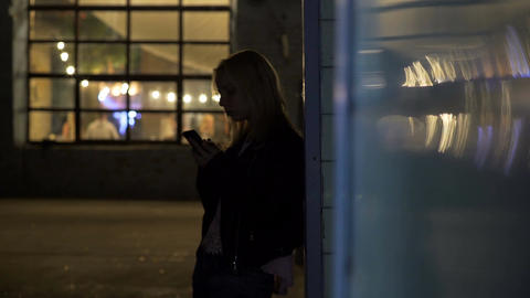 Lonely girl standing on alley near nightclub and calling taxi, night life Footage