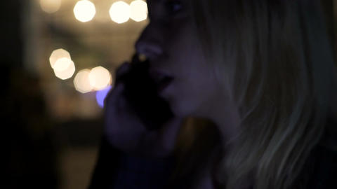 Depressed blond woman standing outside pub and calling boyfriend after fight Footage