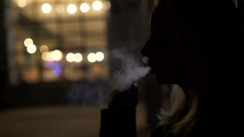 Silhouette of sad woman smoking outside night club, bad habits, depression Live Action