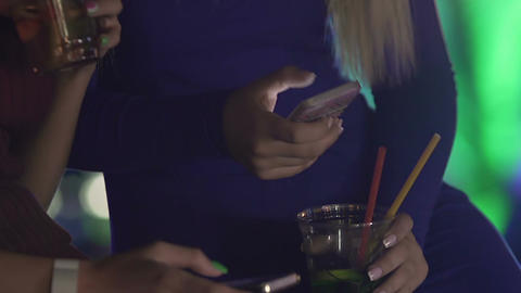 Beautiful young women socializing with friends using phones while having drink Footage