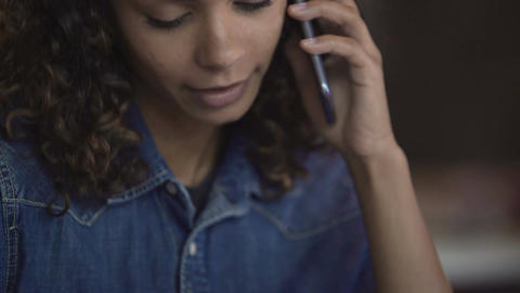 Beautiful curly biracial woman talking on smartphone and smiling, emotions Footage