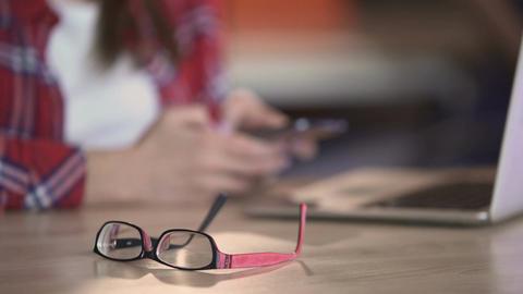 Stylish eyeglasses lying on table, woman texting on smartphone, communication Footage