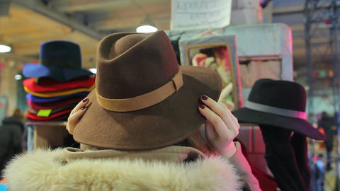 Glamorous lady putting on wide brimmed hat, posing, having fun at local market Live Action