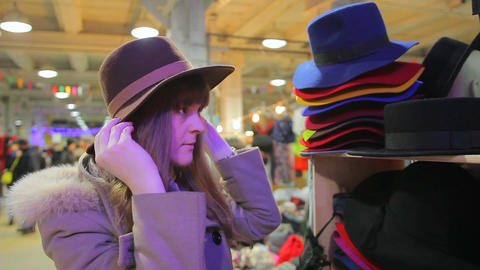 Young attractive female fitting different hats, trying on image of fashion diva Footage