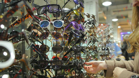 Lady confused with large choice of sunglasses on shopping stands at local market Footage