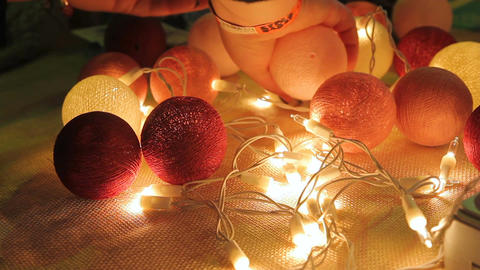 Female hands assembling garland from handmade glowing balls, festive atmosphere Footage