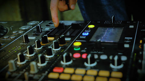 Nightclub DJ adjusting controls, twisting toggle on professional soundboard Footage