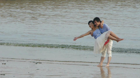 The happy couple at beach.Men picked up woman.tide,tidal Footage