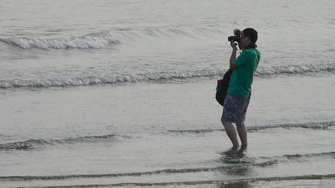photographer taking pictures at sand beach.tide,tidal Stock Video Footage