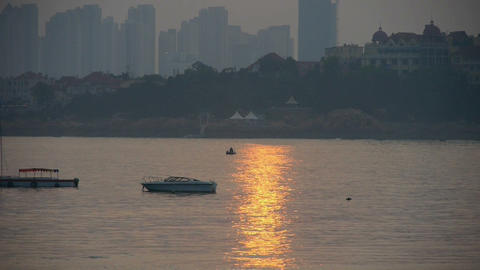 Dusk waterfront.Ship boat on the sea,horizon is high-rise buildings Footage