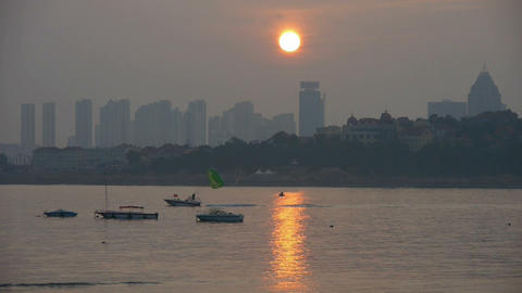 Dusk waterfront.Clipper boat dragging paragliding,horizon is high-rise buildings Footage