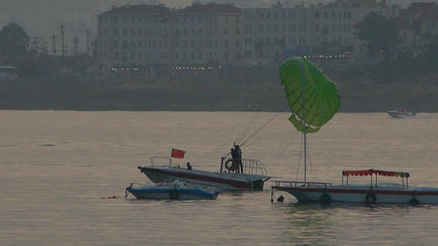 Clipper boat dragging paragliding,horizon is high-rise buildings Footage