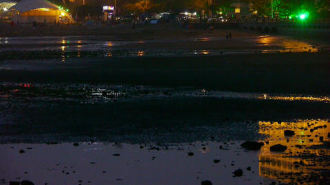 Neon house reflection in inlet.Car traveling on shore.Tourist play at sand beach Footage
