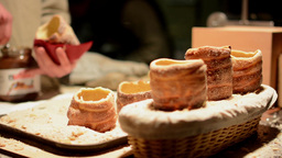 Trdelník (chimney cake or stove cake) in shop (in night) - man in the backgroun Footage