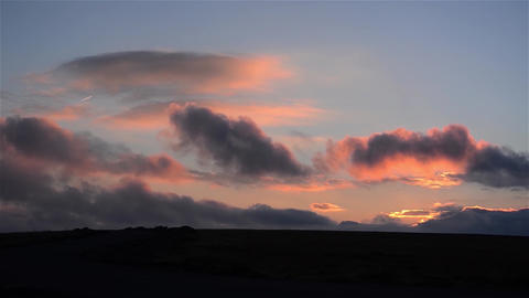 Reddish and gray clouds fleeing driven by wind over some hills Footage