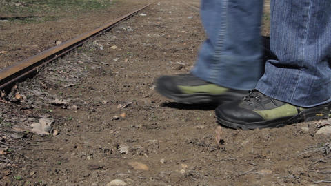 Man wearing green boots cross a railroad in his walk every day Footage