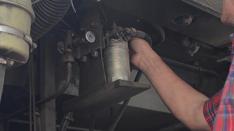 Mechanic who unscrew by hand a screw from the pump of a motor bus Footage