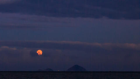 Yellow Moon in Dark Cloudy Blue Sky above Sea Footage