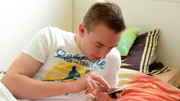 man lies in bed and typing on mobile phone and smiles Footage