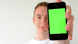 man with a phone (green screen) - man is smiling - man shows phone to camera Footage