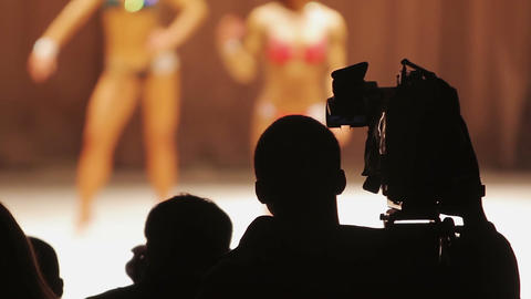 Professional operator filming female bodybuilding competition, camera crew Footage