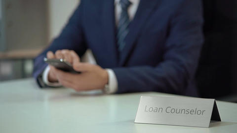Loan counselor using smartphone, providing debt settlement services to client Footage