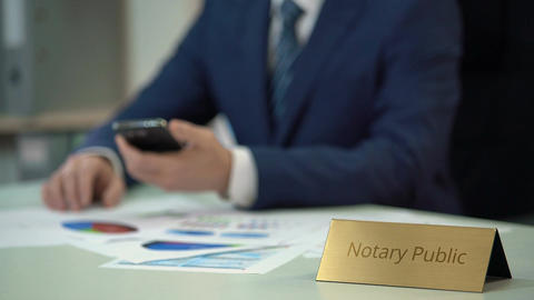 Competent notary public working with documents, checking information on gadget Footage