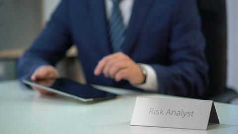 Risk analyst reading market report on tablet pc, checking new project chances Live Action