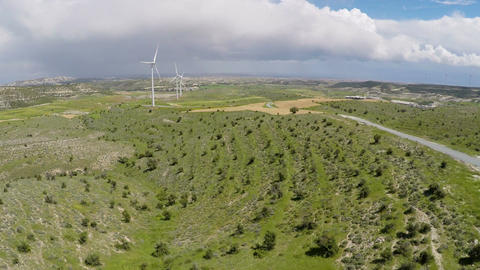 Thick rainy clouds over green landscape and wind farm, weather change forecast Footage