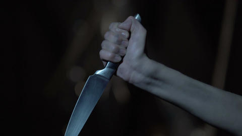Shuddering hand holding knife, psycho maniac committing crime, murder weapon Live Action