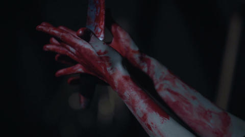 Scary scene, shaky bloody hands of murderer holding knife and dropping, horror Live Action