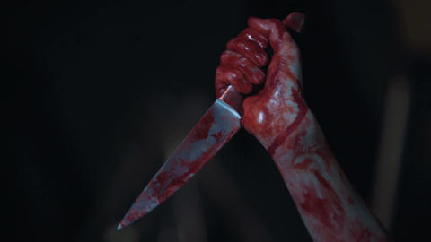 Mad serial killer gripping knife covered in blood, hands of ruthless maniac Live Action