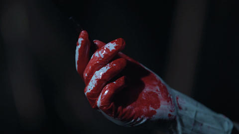 Bloody scalpel in hands of cruel serial killer, violence and crime, horror scene Live Action