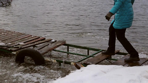 Woman walking dangerously on a destroyed icy pier GIF