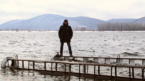 Man standing dangerously on a narrow icy pier GIF