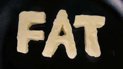 Butter in shape of the word fat melting on hot pan - Close up top view Footage