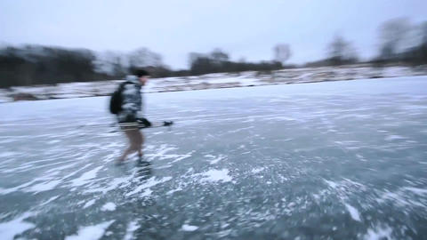 happy guy Ice Skating on a Frozen Lake, with a backpack,… Stock Video Footage